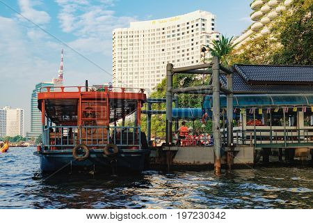 Bangkok, Thailand - January 9, 2016: Oriental Pier is the first pier of Chao Phraya Express Boat popular boat travel and tourist attractions on both sides of the river. CAT Tower is in the background