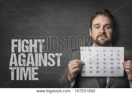 Portrait of confident businessman holding calendar by fight against time text over blackboard