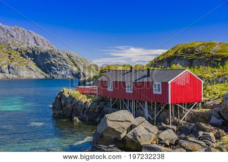 Red Classic Norwegian Rorbu fishing hut with sod roof on Lofoten islands,  Nusfjord. Norwegian traditional type of house used by fishermen