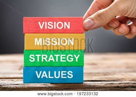 Closeup of hand building colorful blocks of vision mission strategy and values on wood