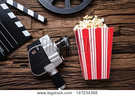 Closeup of movie camera with clapper board and popcorn on wood