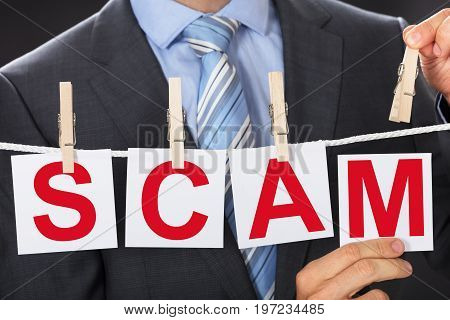 Closeup midsection of businessman pinning SCAM cards on clothesline