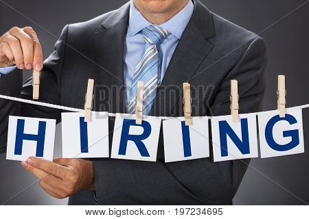 Closeup midsection of businessman pinning HIRING cards on clothesline
