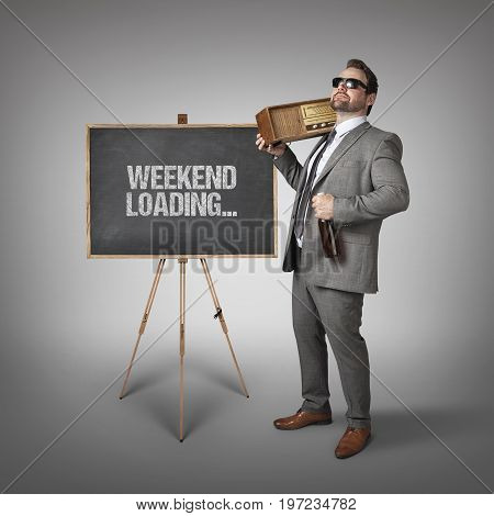 Drunken businessman holding alcohol bottle and radio while standing by blackboard with weekend loading text over gray background