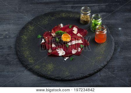 Italian Delicious Antipasto bresaola with oregano, quail egg, onion on stone plate, top view.