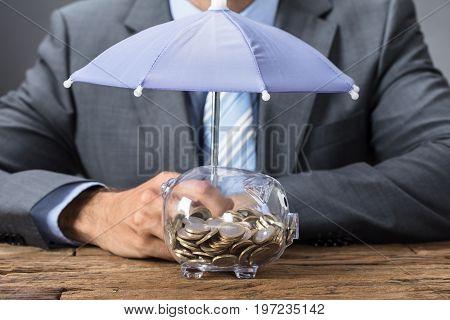 Closeup midsection of businessman sheltering transparent piggybank with umbrella at table