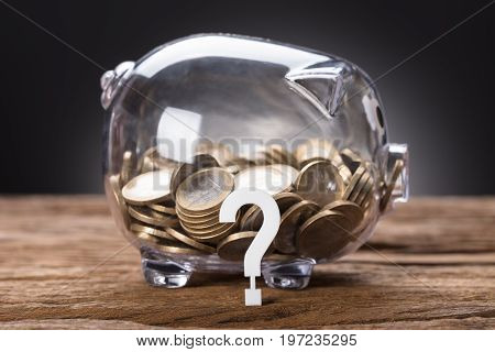 Closeup of question mark and coins in transparent piggy bank on table