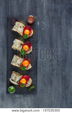 Four tiny appetizers with cured met, yolk and parmegano cheese on stone board with copyspace. Top view.