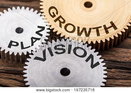 Closeup of plan vision and growth interlocked cogwheels on wood