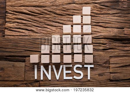 Closeup of invest text by increasing bar graph blocks on wooden table