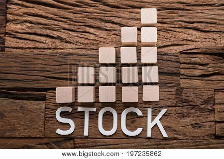 Closeup of stock text by increasing bar graph blocks on wooden table