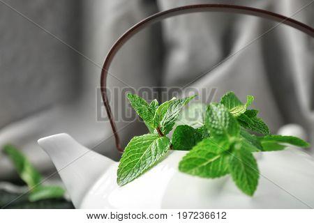 Teapot with fresh lemon balm leaves, closeup