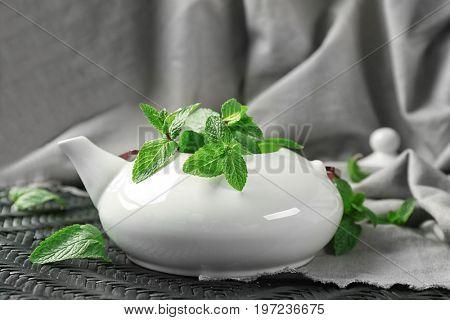 Teapot with fresh lemon balm leaves on table