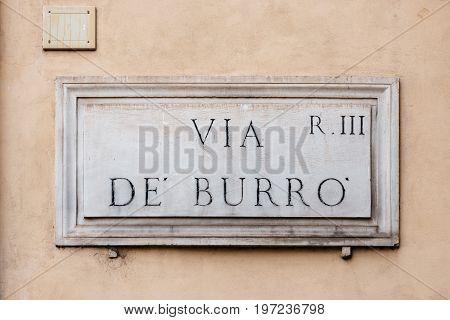 Street name sign in facade of building in Rome. Via de Burro