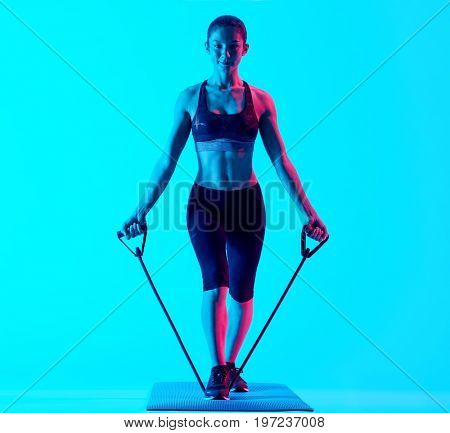 one mixed races woman exercsing fitness elastics  exercices isolated on blue blackground