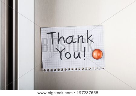 Closeup of thank you note attached with orange magnetic thumbtack on metal
