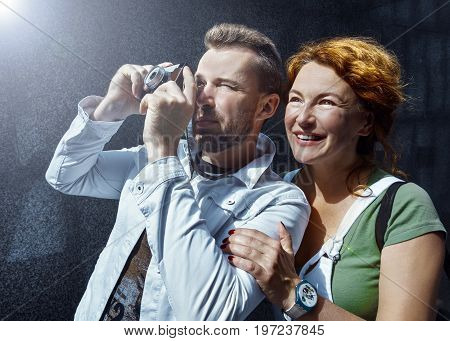 Middle aged couple is having fun on vacantion trip, making a photoshot on an old film camera