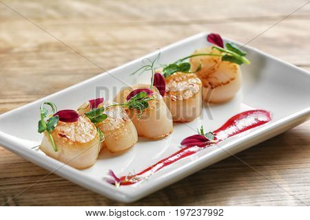 Plate with delicious scallops on table