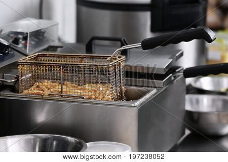 French fries in deep fryer on kitchen