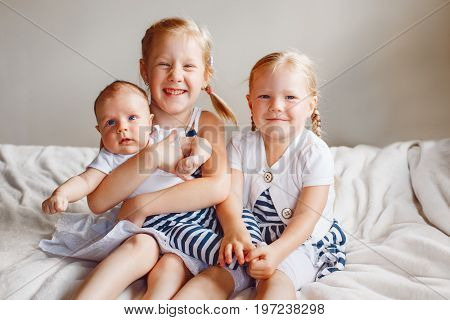 Lifestyle portrait of cute white Caucasian girls sisters holding little baby sitting on bed indoors. Older siblings with younger brother sister newborn. Family love bonding together concept.