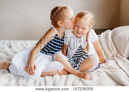 Portrait of two cute adorable little red-haired blonde Caucasian girls sisters sitting together on bed at home. Siblings hugging kissing. Happy lifestyle childhood concept.