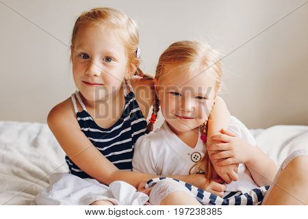 Portrait of two cute adorable little red-haired blonde Caucasian girls sisters sitting together on bed at home. Siblings hugging looking in camera. Happy lifestyle childhood concept.