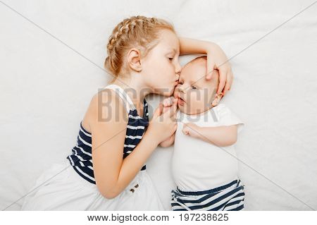 Lifestyle portrait of cute white Caucasian girl sister holding kissing little baby lying on bed indoors. Older sibling with younger brother newborn. Family love bonding together concept.