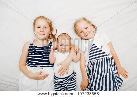 Lifestyle portrait of cute white Caucasian girls sisters holding little baby lying on bed blanket indoors. Older siblings with younger brother sister newborn. Family love bonding together concept.