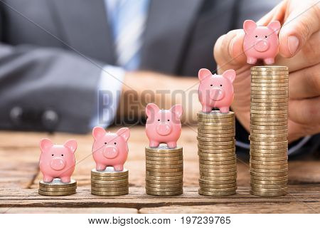 Midsection of businessman placing piggybank on stacked coins in increasing order