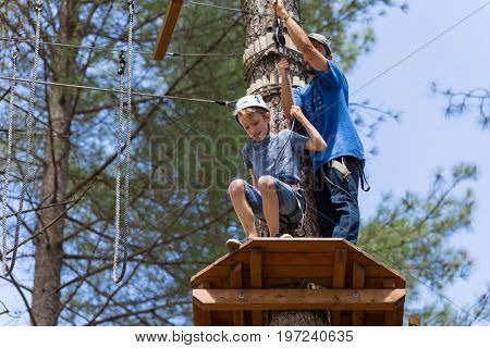 MEZIO, PORTUGAL - JULY 22, 2017: young adventurous kid prepares to   slide in zip lining thru the forest. July 22, 2017, Mezio, Portugal.