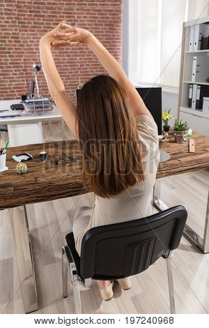 Rear View Of A Businesswoman Sitting On Chair Stretching Her Arms At Workplace