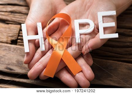 Person's Hand Showing Ribbon With Hope Text To Support Kidney Cancer And Leukemia Awareness