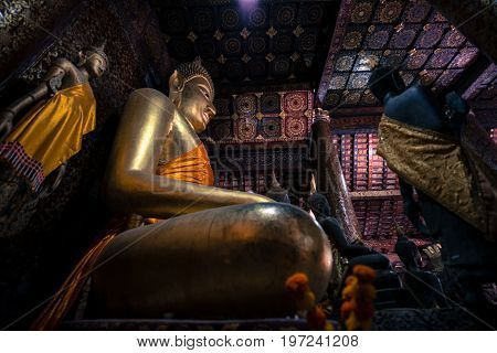 Wide angle picture of sitting Buddha and other images inside Wat Xieng Thong Buddhist temple located in the city Luang Prabang Laos.