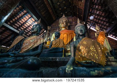 Horizontal picture of sitting Buddha and other images inside Wat Xieng Thong Buddhist temple located in the city Luang Prabang Laos