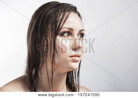 Beauty Concepts and Ideas. Portrait of Caucasian Sensual Brunette Girl Showing Wet and Shining Skin and Wet Hair. Creative Makeup. against Grey. Horizontal Image Orientation