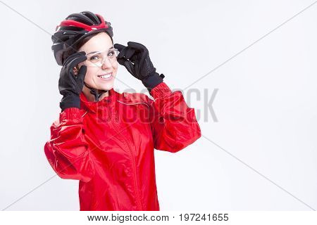 Sport Concepts and Ideas. Portrait of Smiling Caucasian Female Cycling Athlete Posing Equipped in Professional Outfit in Studio. Horizontal Image Composition