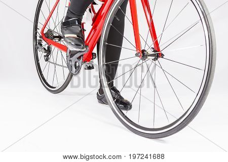 Cycling Concepts. Closeup of Legs of Female Cyclist and Wheels of the Road Bike Placed in Studio. Horizontal Image