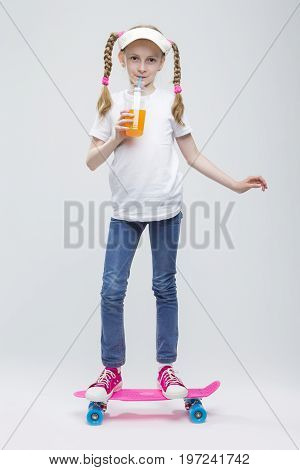 Full Length Portrait of Happy Caucasian Blond Girl in Visor Ballancing on Pennyboard With Cup of Juice.Against White. Vertical Image Composition