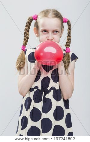 Portrait of Funny Caucasian Blond Girl With Pigtails Posing in Polka Dot Dress Against White. Blowing Up Red Heart Shaped Air Balloon. Vertical Image Orientation