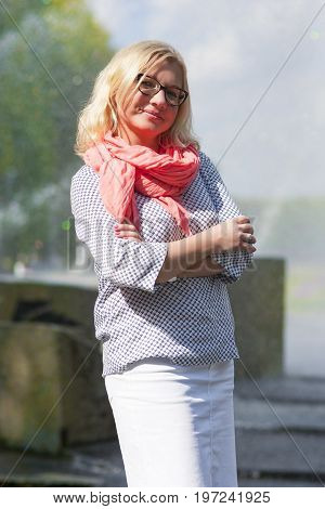 Middle Aged Females Concepts. Portrait of Mature Middle Aged smiling Blond Woman Wearing Spectacles Posing Outdoors in Park.Hands Folded in Front. Vertical Image Composition