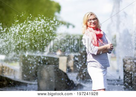 Middle Aged Females Concepts. Portrait of Mature Middle Aged smiling Blond Woman Wearing Spectacles Posing Outdoors in Park.Hands Folded in Front. Horizontal Image Composition