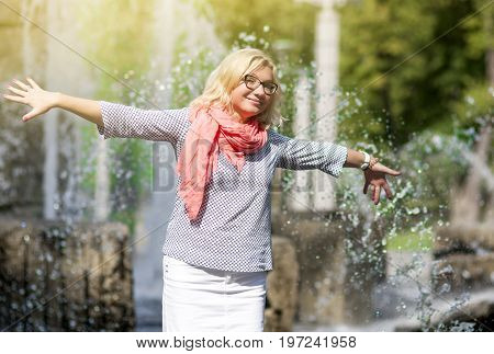 Portrait of Funny Mature Middle Aged Smiling Blond Woman Wearing Spectacles Posing Outdoors in Park. Showing Outstretched hands Against Nature Background.Horizontal Image