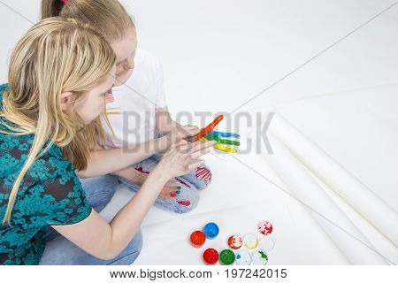 Family Activity Concepts. Mother with Little Daughter Making a Hand Pint Together Indoors.Against White. Horizontal Image Composition