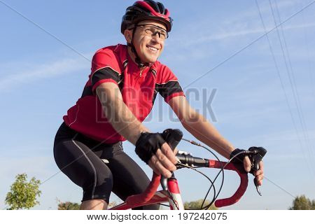 Cycling Concepts. Smiling Professional Road Cyclist During Ride on Bike Outdoors. Completely Equipped in Professional Outfit.Horizontal Shot