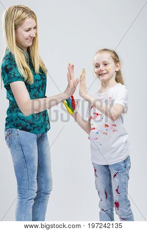 Family Ideas. Portrait of Mother and Her LIttle Caucasian Blond Daughter Having Hand and Face Paint Time Together Indoors.Giving a High Five. Vertical Image