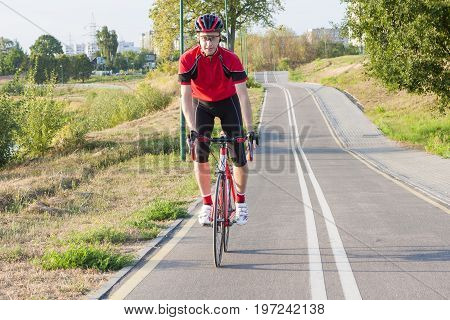 Sport and Cycling Ideas. Portrait of Professional Male Cyclist Doing Uphill Out of the Saddle on Road Bike. Fully Equipped in Professional Outfit. Horizontal Image Orientation