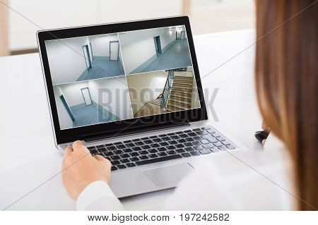 Close-up Of A Businesswoman Monitoring The CCTV Footage Of Office On Laptop