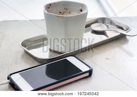 Hot chocolate cup and smart phone stock photo