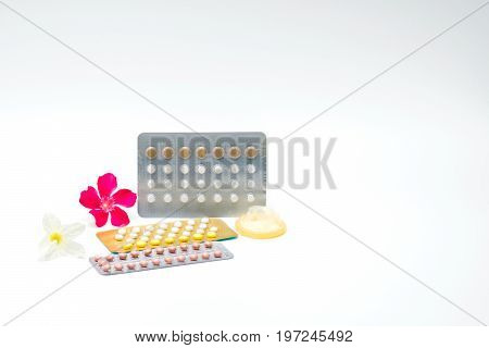 Contraceptive pills and condom with pink flower on white background