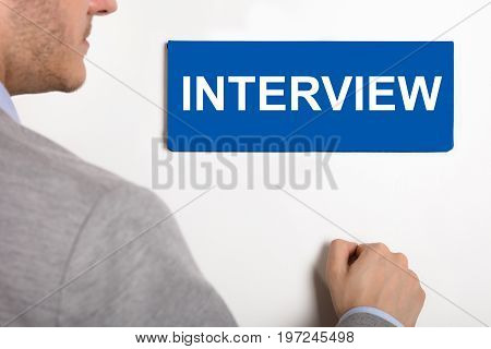 Close-up Of A Young Businessman Knocking White Door With Interview Nameplate